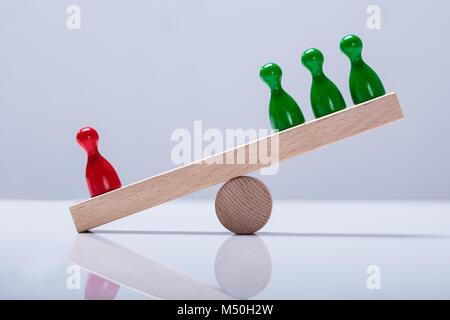 Rote und Grüne Spielfiguren Figuren Balancieren auf Holz- Wippe über den Schreibtisch - Stockfoto