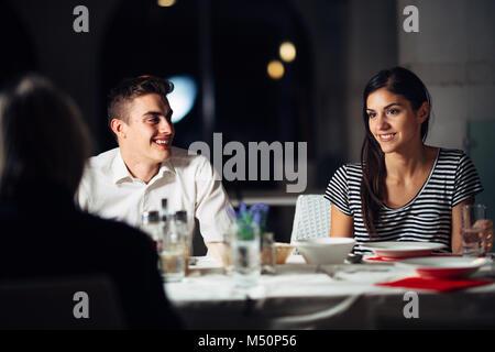 Eine Gruppe von Freunden mit einem Abendessen in einem Restaurant. doppelte Datum. Attraktive Menschen Nacht heraus, Essen in einem Hotel. trendige Leute besucht eine neue geöffnet. B