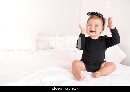 Süße kleine Mädchen in schwarzen Kleidern sitzen auf dem weißen Bett zu Hause. Close up Portrait. Glückliche Kindheit - Stockfoto