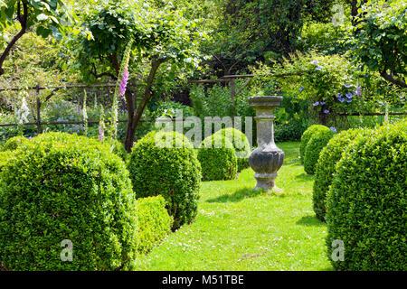 Stein ornament Vase auf einem Gras weg zwischen Buxus abgerundete Formgehölze Stauden, die zu einer Holz- bogen - Stockfoto