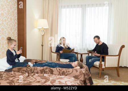Der Mann und die Frau und die Kinder in das Zimmer. Die Kinder sitzen auf dem Bett, Eltern auf Stühlen. Junge Familie - Stockfoto