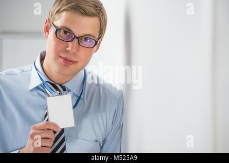 Glücklich lächelnde Geschäftsmann, die leere Plakette, und lehnte sich an der Wand im Büro - Stockfoto