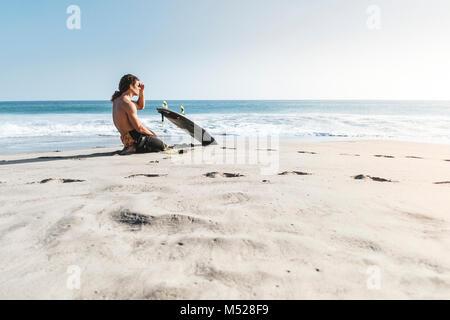 Surfer Sitzen am Strand, Fuerteventura, Kanarische Inseln, Spanien - Stockfoto
