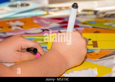 Kleines Mädchen zeichnen ein Bild von playcard - Stockfoto