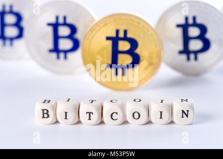 Einzelnes Wort BITCOIN aus Holzklötzen mit mehreren goldenen und silbernen Bitcoin Münzen stehen auf weißen Hintergrund, - Stockfoto