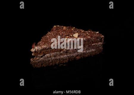 Dreieckigen Kuchen mit Schokolade bestreuen auf einem dunklen Hintergrund - Stockfoto