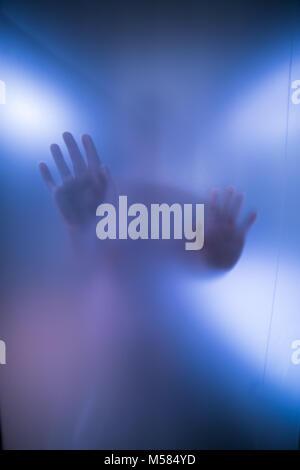 Silhouette der Frau die Hände hinter blauen Glas - Stockfoto