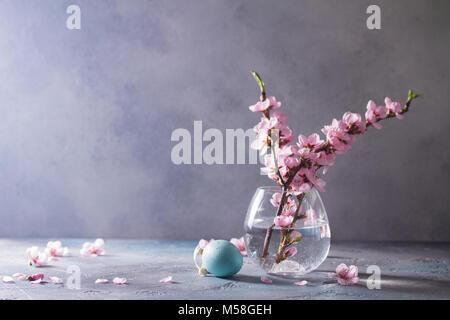 Ostereier und Pink Cherry Blossom Zweige posy in Glasvase auf grauem Hintergrund mit Kopie Raum - Stockfoto
