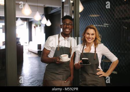 Männliche und weibliche Barista am Eingang der Coffee Shop holding Kaffeetassen. Happy coffee shop besitzer mit - Stockfoto