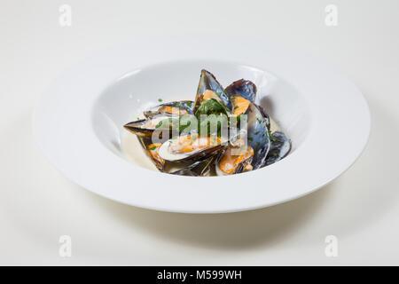Muscheln in eine cremige Soße in einer weißen Schüssel auf weißem Hintergrund - Stockfoto