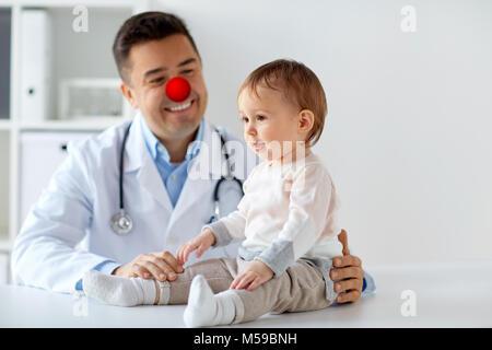 Happy Baby Mädchen an Arzt auf red nose day - Stockfoto