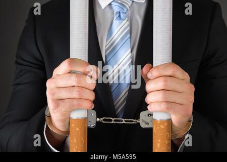 Mittelteil der Geschäftsmann Holding big Zigaretten beim Tragen von Handschellen auf schwarzem Hintergrund - Stockfoto