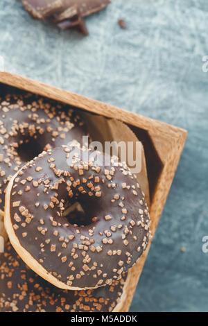 Schokolade Donuts in einem hölzernen Kasten auf einem grauen strukturierten Hintergrund. Flach. - Stockfoto
