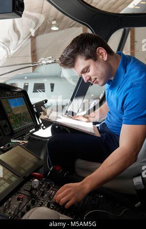 Männliche Aero Ingenieur mit der Zwischenablage arbeiten In Helicopter Cockpit - Stockfoto