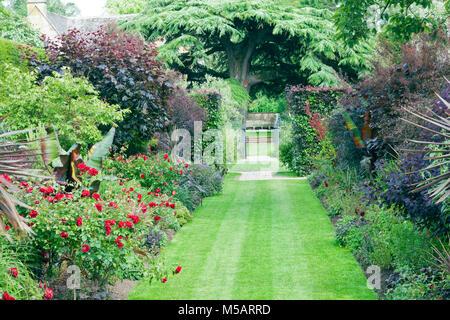 Gras weg zwischen Blumenbeeten mit roten Rosen und blühende Pflanzen, Kräuter, die zu einem Metall Tor und Holzbank - Stockfoto