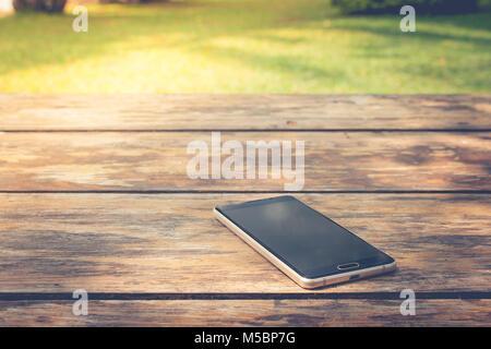 Vergessen und Verlieren Konzept: BlackBerry-Smartphone auf Holztisch im öffentlichen Park. - Stockfoto