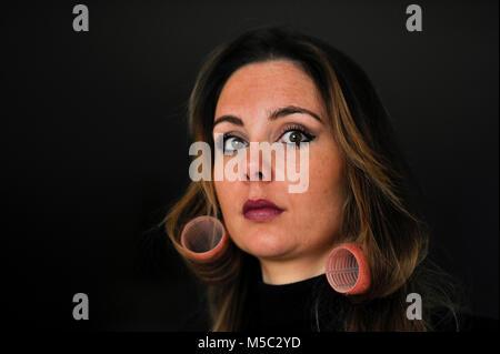 Schöne junge Frau mit Brünette Haar Haar Rollen gegen den dunklen Hintergrund - Stockfoto