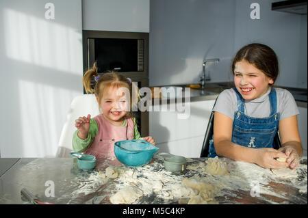 Zwei kleine Mädchen Kochen in der Küche. Die Kinder sitzen am Tisch. Kneten Sie den Teig. Hände und Gesichter von - Stockfoto