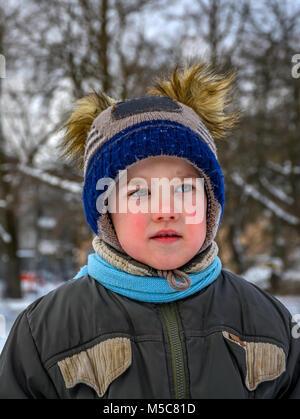 Ein kleiner Junge spielt auf dem Spielplatz. Einen Spaziergang an einem Wintertag. - Stockfoto