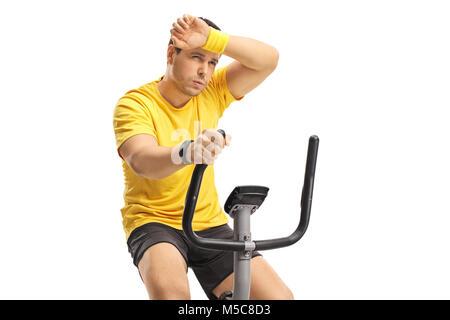 Müde junge Mann Ausübung auf einem Cross-trainer Maschine auf weißem Hintergrund - Stockfoto