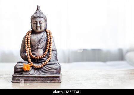 Buddha Statue mit Perlen. Buddha Statue in helles Zimmer. - Stockfoto