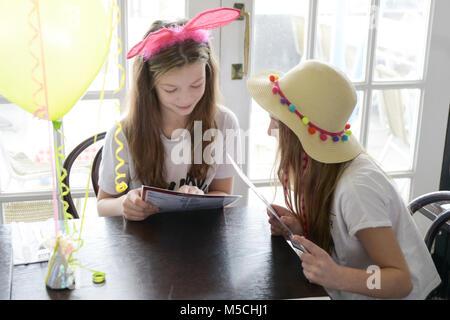 Zwei kleine Kinder sitzen auf einer Party Tisch essen gebratene Nahrung und trinken Milchshakes - es gibt Ballons - Stockfoto