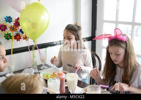 Vier junge Kinder sitzen auf einer Party Tisch essen gebratene Nahrung und trinken Milchshakes - es gibt Ballons - Stockfoto