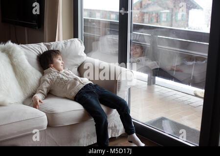 Vorschule Junge, sitzt am Fenster im Wohnzimmer, mit Blick auf die verschneite Landschaft im Freien, im Winter schneit - Stockfoto