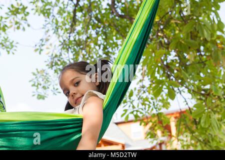 Portrait zuversichtlich Mädchen in grün Hängematte - Stockfoto