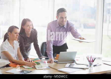 Junge Geschäftsleute am Schreibtisch arbeiten in kreativen Büro - Stockfoto