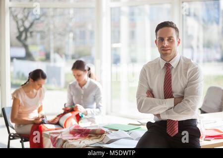Portrait von selbstbewussten jungen Geschäftsmann mit weiblichen Kollegen, die im Hintergrund bei Büro - Stockfoto