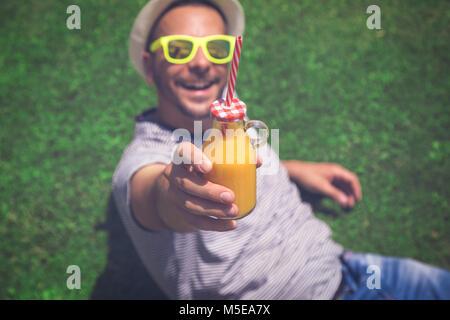 Portrait von jungen Mann liegen auf dem Feld und ein Glas frisch gepressten Orangensaft. Sommer und gesunden Lebensstil - Stockfoto