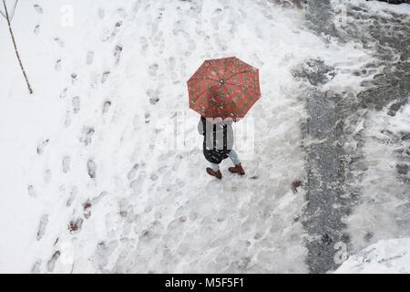 Frau mit einem roten Regenschirm auf verschneiten Tag Top View Point - Stockfoto