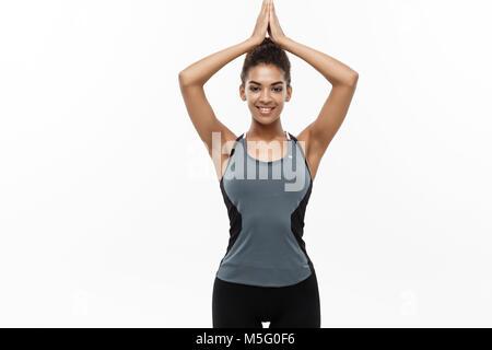 Gesunde und Fitness Concept - Schöne amerikanische afrikanische Dame fitness Kleidung Yoga und Meditation. Auf weissem - Stockfoto