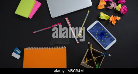 Das zusammengesetzte Bild im Laptop, Handy und Schreibwaren auf schwarzem Hintergrund - Stockfoto