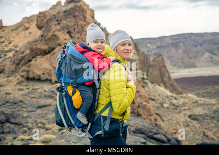 Familienwanderung baby boy in der Mutter Rucksack reisen. Wandern Abenteuer mit Kind auf Herbst Familie Reise in - Stockfoto