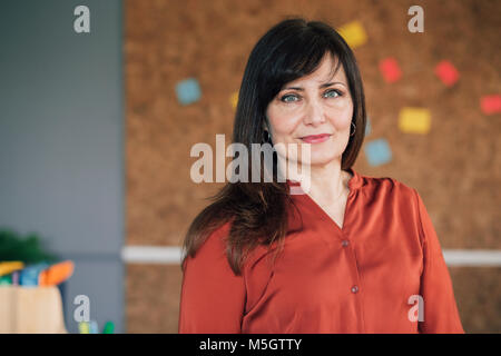 Porträt eines reifen, weibliche Unternehmer in Ihrem Büro. Sie steht vor einem Cork board und ist elegant gekleidet, - Stockfoto