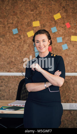 Porträt einer schönen Frau in ihren Arbeitsplatz. Sie steht vor einer Pinnwand und ist elegant gekleidet, Lächeln - Stockfoto
