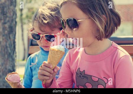 Zwei kleine Mädchen (Schwestern) Eis essen. Stockfoto