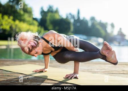 Frau praktizieren Yoga auf Steg am See - Stockfoto
