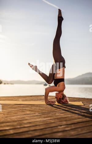 Praktizierende frau yoga auf Steg am See tun ein Kopfstand - Stockfoto