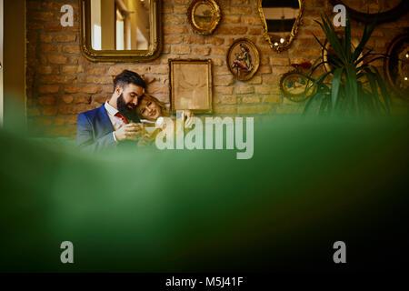 Elegantes Paar mit Getränken sitzen auf der Couch umarmt - Stockfoto