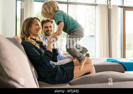 Glückliche Eltern spielen mit Sohn auf dem Sofa zu Hause - Stockfoto