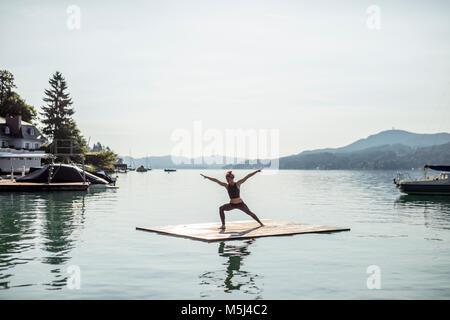 Praktizierende frau yoga auf floss in See - Stockfoto