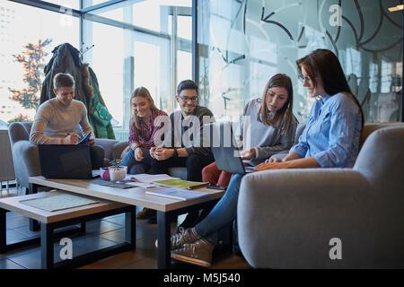 Eine Gruppe von Freunden zusammen sitzen in einem Café mit Laptop und Dokumente - Stockfoto