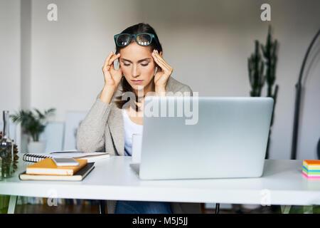 Junge Frau mit Laptop auf dem Schreibtisch ihr Tempel berühren - Stockfoto