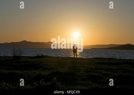 Eine Frau sieht den Sonnenuntergang in der Nähe von Oakland, CA - Stockfoto