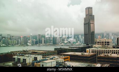 Eine Frau touristische schaut aus Ihrem Hotelzimmer im Hotel Icon an der Skyline von Kowloon, Hong Kong an einem - Stockfoto