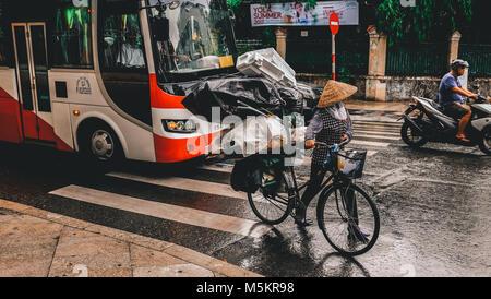 Eine Frau geht durch den Verkehr mit vielen Dinge mit ihr Fahrrad in Vietnam, Ho Chi Minh. - Stockfoto