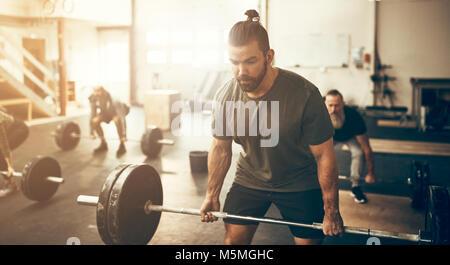 Passen junge Mann in Sportkleidung Anstrengung beim Heben schwerer Gewichte beim Training in einem Fitnessstudio - Stockfoto